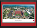 Picture: Arkansas Razorbacks Donald W. Reynolds Razorback Stadium panoramic poster professionally double matted in team colors and framed. This aerial panorama of the University of Arkansas was taken by James Blakeway during an Arkansas Razorback football game. Centered in the panorama is Donald W. Reynolds Razorback Stadium. Originally named Bailey Stadium in 1938, it was renamed Razorback Stadium in 1941. After a $20 million contribution to the 2001 stadium expansion by the Donald W. Reynolds Foundation, capacity increased to 72,000. The University, founded in 1871 in Fayetteville, Arkansas on a hilltop farm overlooking the Ozark Mountains, is home to one of the most beautiful assemblages of collegiate athletic venues in the Southeastern Conference, including Bud Walton Arena, the football practice fields and the John McDonnell Track Field.