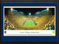 Picture: Michigan Wolverines Michigan Stadium 13.5 X 40 panoramic print professionally double matted in team colors and framed to 18 X 44. This panorama, taken by James Blakeway, captures a historical moment as the Michigan Wolverines played their first night game at the Big House on September 10, 2011. The event set a new Michigan Stadium and NCAA attendance record with a crowd of 114,804 fans. To further celebrate the occasion, the team wore �legacy' uniforms highlighting design elements from past eras, including a large �M' on the front of the jersey and numbers on the sides of the helmet. In the 39th meeting between the schools, Michigan defeated Notre Dame 35-31 with the final touchdown recorded in the last seconds of the game. Michigan now holds a 23-15-1 advantage in the classic rivalry.