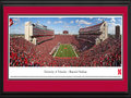 Picture: Nebraska Cornhuskers Memorial Stadium 13 X 40 panoramic print professionally double matted in team colors and framed to 18 X 44. This panorama, taken by Sheila Gjevre, shows a �Sea of Red� as the Nebraska Cornhuskers football team play for another victory in Memorial Stadium. Since 1923, Memorial Stadium has been the home to Huskers football and continues to provide one of the most exciting game day experiences in all of college football. Today, after completion of the East Stadium expansion, the stadium seats over 92,000 fans. Rich with tradition, Husker fans continue to celebrate the first score of every home game with the release of red balloons into the sky. The University of Nebraska-Lincoln, chartered in 1869, was one of the first institutions west of the Mississippi River to award doctoral degrees.