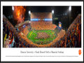 "Picture: Just out from October 3, 2015 is a 13.5 X 40 panoramic poster of Frank Howard Field at Memorial Stadium professionally framed to 13.75 X 40.25. In this game the Clemson Tigers take an exciting 24-22 win over #6 ranked Notre Dame on ABC. This panorama of Frank Howard Field at Memorial Stadium, taken by James Blakeway, spotlights the excitement after a rain-soaked football match-up between two collegiate powerhouses, the Clemson University Tigers and Notre Dame. Despite the rain, Clemson fans packed Death Valley with orange ponchos and rain boots to cheer the Tigers to victory. The trademark Clemson colors are brilliantly on display, as Tiger fans ""Gather at The Paw� following a big win."