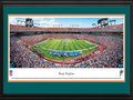 Picture: This 13.5 X 40 panorama of the Miami Dolphins playing to a capacity crowd at Sun Life Stadium has been professionally double matted in team colors and framed to 18 X 44. Originally known as Joe Robbie Stadium, Sun Life Stadium is a multi-purpose stadium in the South Florida suburb of Miami Gardens and the first of its kind in the NFL to be constructed entirely with private funds. The Dolphins began play in the American Football League (AFL) as an expansion team in 1966 and are the oldest major-league professional sports franchise in the state of Florida. In 1972, the Dolphins completed the NFL's first perfect season, culminating a 17-0 record with a win in Super Bowl VII. They were also the first team to appear in three consecutive Super Bowls. From the NFL Stadiums collection.